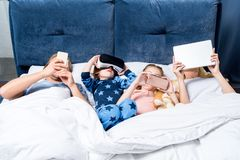 молодая семья с 2 детьми используя устройства пока лежащ совместно стоковые фото