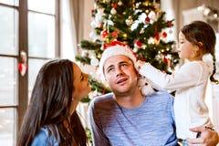 Молодая семья с дочерью на рождественской елке дома Стоковые Изображения RF