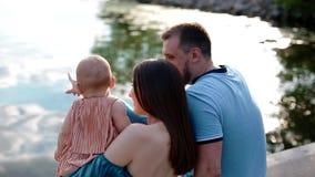 Молодая семья с маленьким ребенком около реки акции видеоматериалы