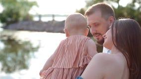 Молодая семья с маленьким ребенком около реки сток-видео