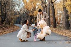 Молодая семья с меньшей дочерью на bi дороги парка осени присутствующем стоковая фотография rf