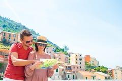 Молодая семья с bacground карты большой взгляд на старой деревне Riomaggiore, Cinque Terre, Лигурии, Италии европейско стоковые изображения rf