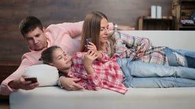 Молодая семья тратя время с электронными устройствами сток-видео
