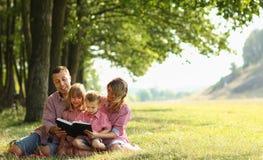 Молодая семья читая библию в природе стоковое изображение