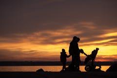 Молодая семья silhouetted против захода солнца океана стоковые изображения rf