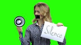 Молодая сердитая женщина со связанным тесьмой ртом