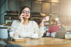 Молодая серьезная коммерсантка в стеклах сидя в кафе на деревянном столе и говоря на сотовом телефоне Стоковое фото RF