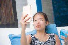 Молодая сладостная и довольно азиатская китайская женщина сидя на курорте пляжа фотографируя selfie на мобильном телефоне счастли Стоковое Изображение