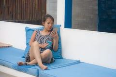 Молодая сладостная и довольно азиатская китайская женщина сидя на курорте пляжа используя средства массовой информации интернета  Стоковое Изображение