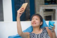 Молодая сладостная и довольно азиатская китайская женщина сидя на holi пляжа Стоковые Изображения