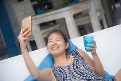 Молодая сладостная и довольно азиатская китайская женщина сидя на holi пляжа Стоковое фото RF