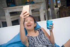 Молодая сладостная и довольно азиатская китайская женщина сидя на holi пляжа Стоковое Изображение