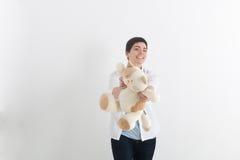 Молодая смеясь над женщина с короткими волосами в непринужденном стиле давая переднего кота игрушки плюша и смотря камеру с улыбк Стоковая Фотография RF