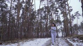 Молодая спортсменка смотрит на ее наручных часах и продолжает побежать в лесе видеоматериал