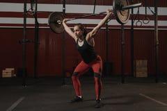 Молодая спортсменка crossfit поднимая тяжелые накладные расходы штанги на спортзал Сильная женщина стоковые изображения rf