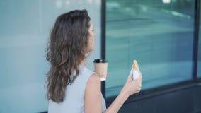 Молодая справедливая женщина волос есть круассан и выпивая кофе проходя путем строить видеоматериал