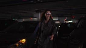 Молодая стильная женщина выходит автомобиля, закрывает ее и идет к месту для стоянки сток-видео