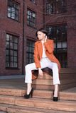 Молодая стильная женщина в красном пальто и белых брюках сидя на деревянных лестницах стоковое фото