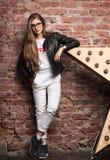 Молодая стильная женщина представляя против старой кирпичной стены Белые брюки и черная кожаная куртка Стоковое Изображение RF