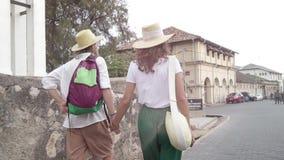 Молодая стильная пара в соломенных шляпах идет улица видеоматериал