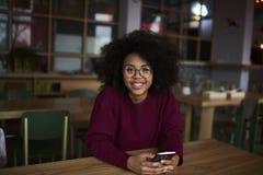 Молодая студентка воссоздавая занимаясь серфингом интернет и беседуя в социальной сети Стоковые Изображения