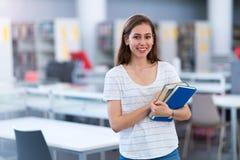 Молодая студентка изучая в библиотеке Стоковые Изображения RF