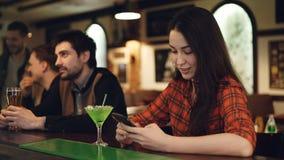 Молодая студентка использует smartphone сидя в причудливом баре с коктеилем Она касающий экран и усмехаться самомоднейше сток-видео