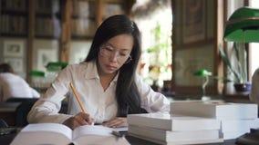 Молодая студентка пишет сидеть на таблице с книгами в библиотеке сток-видео