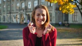 Молодая студентка потревожена и нервнася, с ее пальцами пересеченными перед экзаменом, вне университета акции видеоматериалы