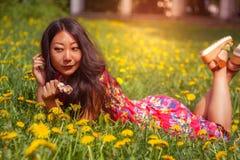 Молодая счастливая азиатская женщина в поле с одуванчиками в луге солнечный день стоковая фотография rf
