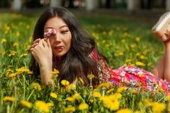 Молодая счастливая азиатская женщина в поле с одуванчиками в луге солнечный день стоковая фотография