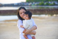 Молодая счастливая азиатская китайская мать женщины прелестного ребенка держа ее сладкую маленькую дочь в ее оружиях принимая про стоковая фотография
