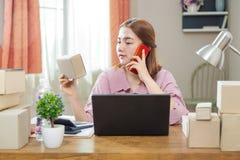 Молодая счастливая азиатская онлайн бизнес-леди в ее доме говоря на h Стоковое Изображение