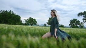 Молодая счастливая белокурая девушка бежит на зеленом пшеничном поле в вечере на фоне неба дождя r сток-видео