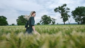 Молодая счастливая белокурая девушка бежит на зеленом пшеничном поле в вечере на фоне неба дождя r акции видеоматериалы