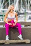 Молодая счастливая белокурая девушка делая спорт в городе стоковые фотографии rf