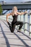 Молодая счастливая белокурая девушка делая спорт в городе стоковые изображения