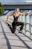 Молодая счастливая белокурая девушка делая спорт в городе стоковое изображение rf