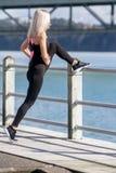 Молодая счастливая белокурая девушка делая спорт в городе стоковая фотография rf
