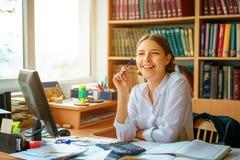 Молодая счастливая дама дела в белой рубашке сидя на таблице с рабочей Средой компьютера и бумаг стоковые фото