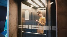 Молодая счастливая девушка входит в лифт, нажимает кнопку, дверь закрывает и она едет вверх по использованию smartphone app и усм видеоматериал