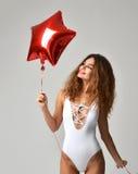 Молодая счастливая девушка с красным воздушным шаром звезды как настоящий момент для дня рождения стоковые изображения