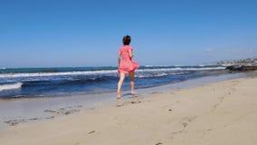 Молодая счастливая женщина бежать вдоль представлять пляжа моря Сильные волны ударяя берег Женщина нося красное baref платья и со акции видеоматериалы