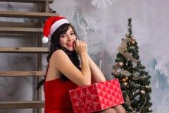 Молодая счастливая женщина в шляпе santa и в красном платье с коробкой g Стоковое фото RF
