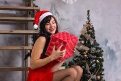 Молодая счастливая женщина в шляпе santa и в красном платье с коробкой g Стоковое Фото