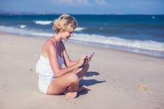 Молодая счастливая женщина говоря на мобильном телефоне на пляже с ба моря стоковые изображения