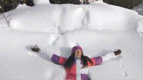 Молодая счастливая женщина делая ангела снега видеоматериал