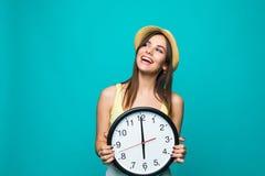 Молодая счастливая женщина держа часы с часами 12 на зеленой предпосылке Портрет положительной милой молодой женщины с на настенн Стоковые Изображения