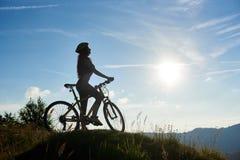 Молодая счастливая женщина задействуя на горном велосипеде на летнем дне Стоковые Изображения