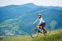 Молодая счастливая женщина задействуя на горном велосипеде на летнем дне Стоковое фото RF
